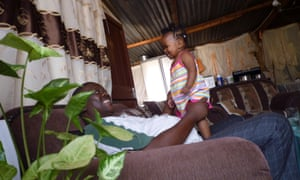 Bhekisisa, Johannesburg, South Africa, sitting on a sofa, holding his daughter, one of a series of self-portraits by people living with HIV