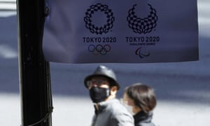 People wearing protective masks to help curb the spread of the coronavirus walk near a banner of Tokyo 2020 Olympic and Paralympic Games Wednesday, March 3, 2021, in Tokyo.