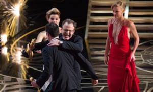 Josh Singer and Tom McCarthy embrace after winning best film for Spotlight.