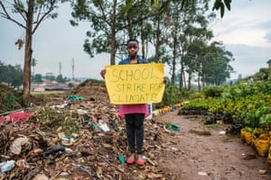 Kampala, Uganda: Leah Namugerwa, a 15 year-old climate activist, with a placard to raise awareness about climate change and the environment. She misses school every Friday as a protest and has full support from her father