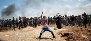 A Palestinian demonstrator in Abu Safia throws a stone towards Israeli positions