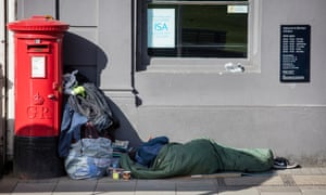 A homeless person in Windsor attempts to rest outside a bank in the town.