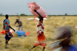 Villagers collect food aid dropped from a plane in gunny bags from a plane onto a drop zone at a village in Ayod county, South Sudan