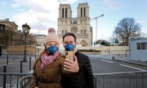 Tourists wearing protective masks take a selfie in front of Notre Dame cathedral