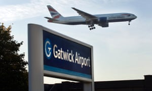a BA plane flies over the Gatwick airport sign