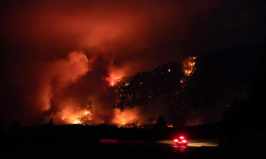 A motorist travels on the Trans-Canada Highway as a wildfire burns on the side of a mountain in Lytton, British Columbia, on Thursday.
