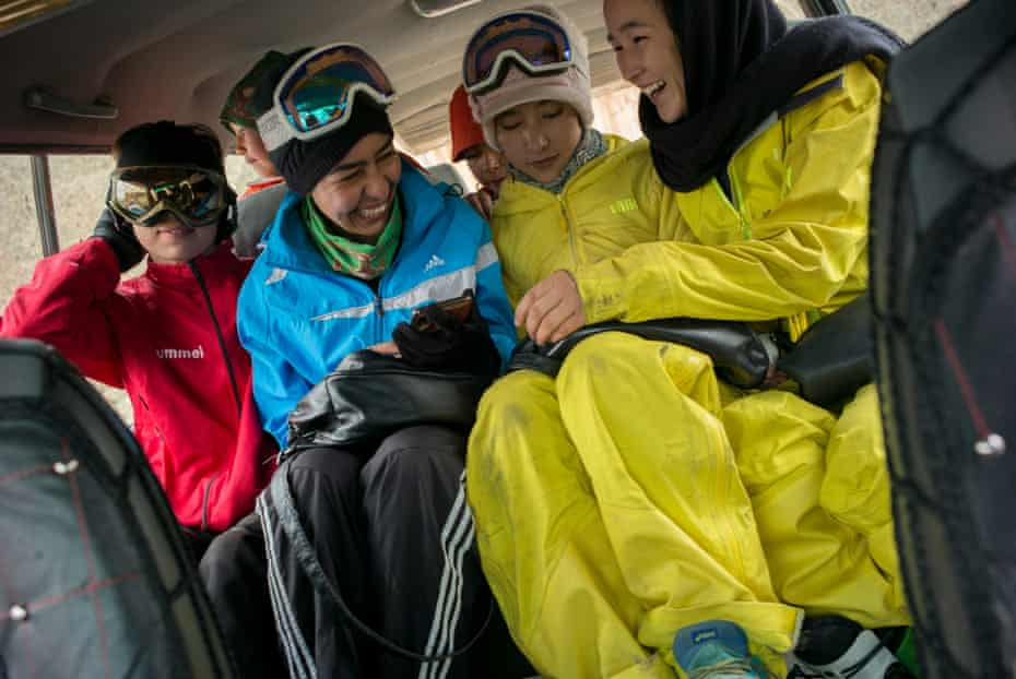 Girls share a joke as they laugh about something on their mobile phone on the way to the mountains.