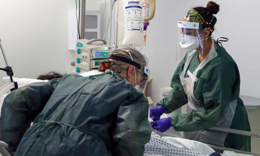 Nurses care for a patient in an intensive care ward treating victims of the coronavirus in Surrey