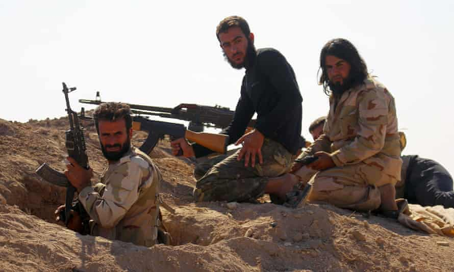 Rebel fighters in Hama province, Syria, carry weapons as they take positions to fight against Assad forces