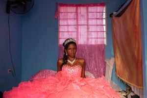 A girl sits on her bed in a princess-like quinceañera outfit