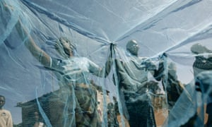 Villagers look at new mosquito nets given to them by Roll Back Malaria Expedition, Matongo, Zambia.
