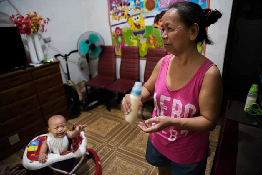 Felicidad prepares formula in her neice's home for grandson Dashiell in Caloocan city, Metro Manila, the Philippines.