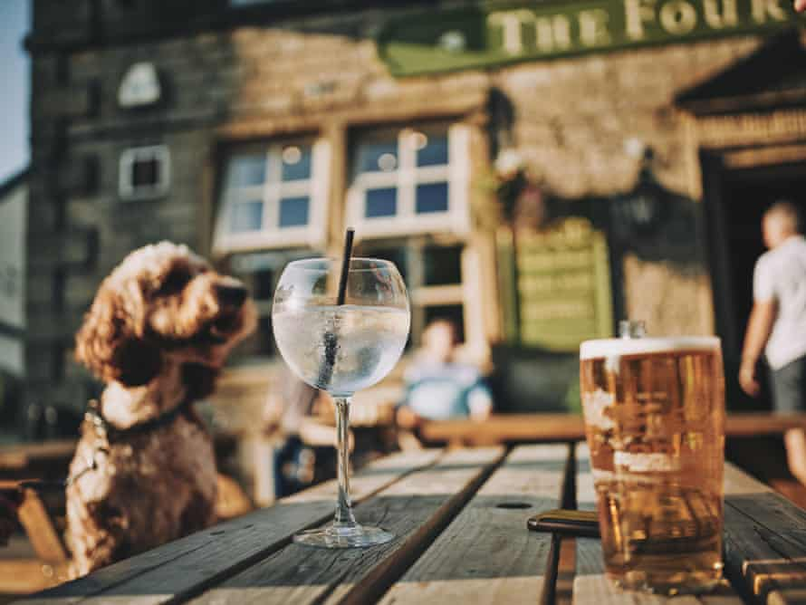 Exterior photograph of The Four Alls Inn, Lancs, UK. A dog is sat on an outside bench looking at a glass of spirits and a pint of beer.
