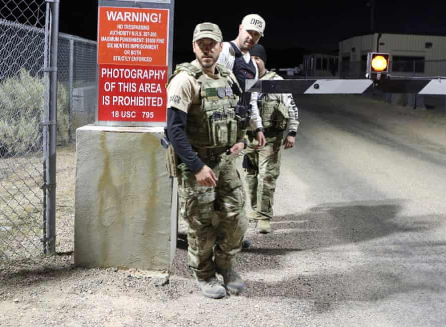 Law enforcement monitor a gate to Area 51.