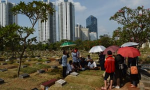 A family pray over a tomb of departed relatives at a cemetery in Jakarta, Indonesia.