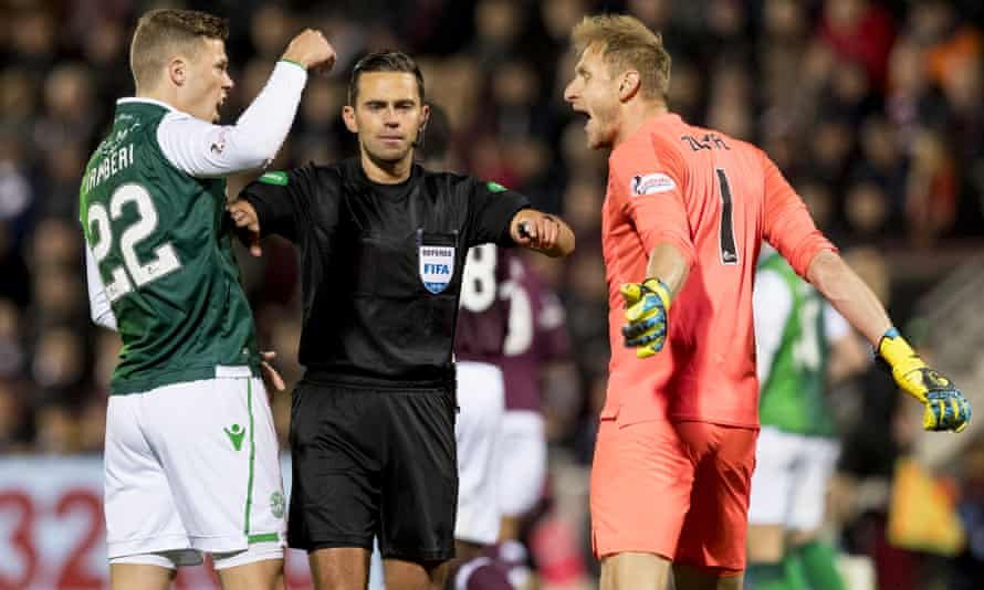 Referee Andrew Dallas breaks up an argument between Florian Kamberi of Hibernian and Zdenek Zlamal of Hearts.