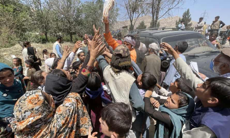 People reach for blankets being handed out in a Kabul park