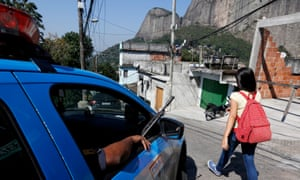 A woman walks past an armed police patrol in Rio de Janeiro's Rochina favela community.