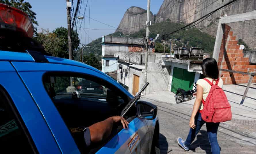 A woman walks past an armed police patrol in Rio de Janeiro's Rochina favela community.