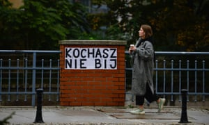 A woman in Wroclaw, Poland, walks by a poster inspired by Les Colleuses, that says: 'You love, you don't hit.'