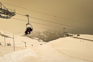 Skiers wearing protective face masks sit on a chairlift as Sahara sand colours the snow and the sky