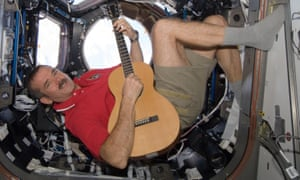 Chris Hadfield plays the guitar, in space, wearing socks, shorts and a polo shirt.