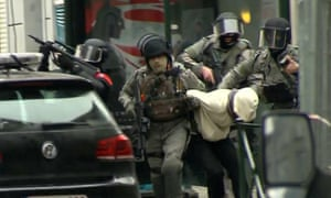 Members of the security force take a suspect to a police vehicle during a raid in the Molenbeek district of Brussels on Friday.