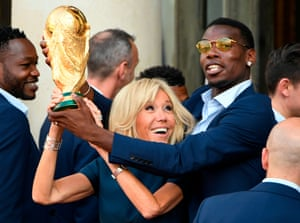 French President Emmanuel Macron's wife Brigitte Macron (C) holds the trophy next to France's midfielder Paul Pogba (R) during a reception at the Elysee Presidential Palace in Paris
