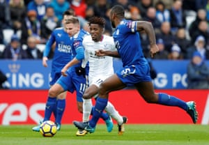 Crystal Palace's Wilfried Zaha surges past Leicester City's Marc Albrighton as Leicester captain Wes Morgan comes across to help.