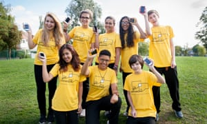 A group of eight young people hold up phones while wearing yellow t-shirts