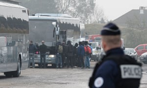 Migrants board buses after registering at a processing centre near Calais