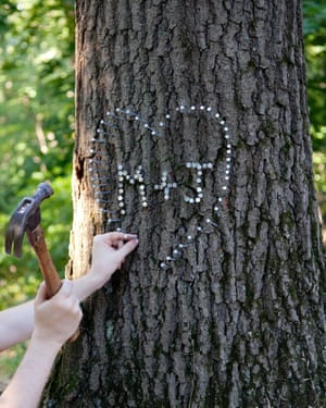 A woman hammering initials and a heart made of nails into a tree, from photographer Olivia Locher's I Fought the Law series