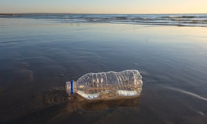 A plastic bottle littering a beach in Melbourne, Australia. Sunset and horizon line in the background.