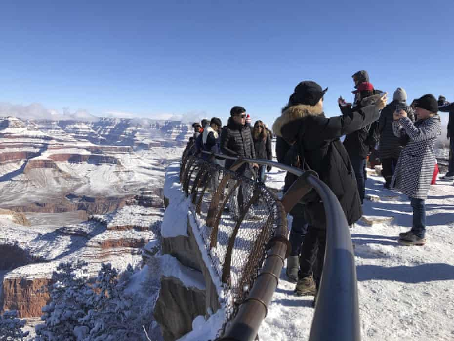 Tourists take photos of a snow-covered Grand Canyon, which state officials have helped keep open.