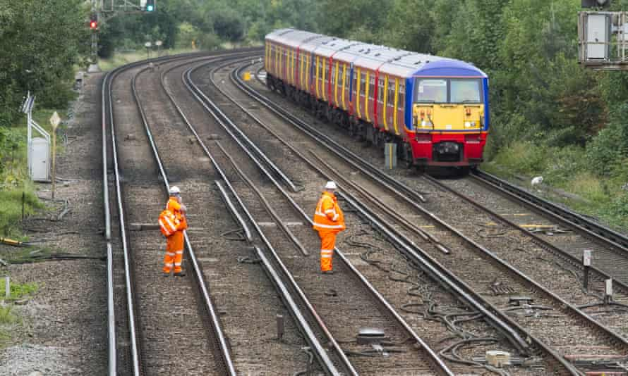 A train passes track workers