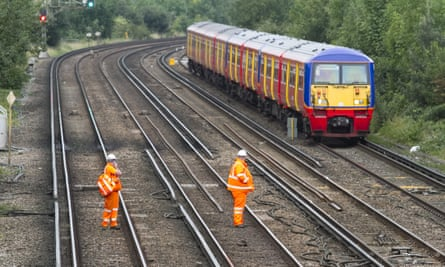 Two rail maintenance men watch a train go by.