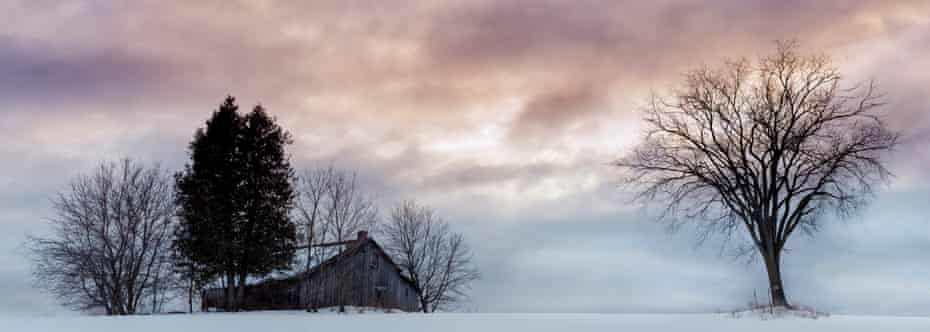 Panoramic view of old barn in winter landscape under overcast sky