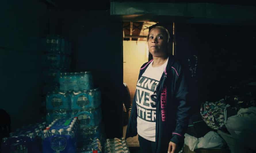 Flint resident Nakia Wakes at home, where she has stored bottled water for her family.