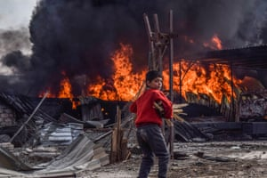 Newcomer: War Notes by Mouneb Nassar. Syrian-born Mouneb Nassar documents the conflict in his country, here a boy collects firewood in the aftermath of airstrikes in Duma.