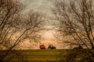 Around sunset a tractor is framed driving between two bare trees by the river Avon in Warwickshire, UK.