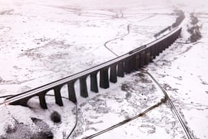 A train passes over the Ribblehead Viaduct in the snow.