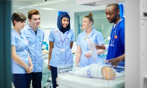 medical students with paediatric doctor<br>four young medical students use a baby simulator mannequin as they work through procedure supervised by a male senior staff nurse