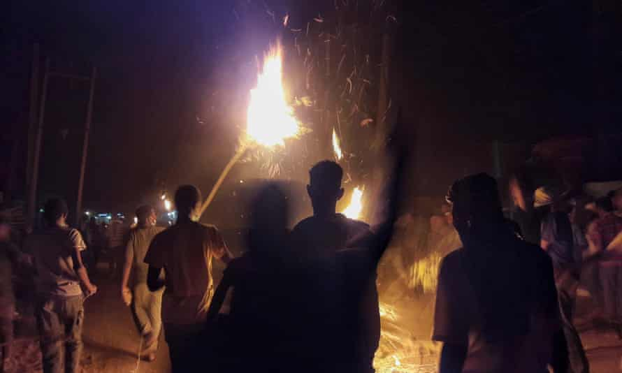 Demonstrators carry torches during an anti-government protest in the Bahri district of Khartoum, the Sudanese capital