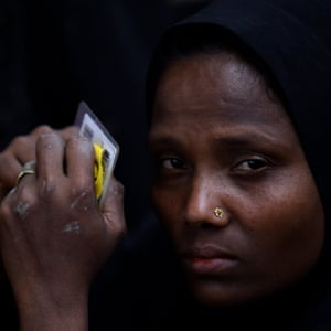 A Rohingya woman holds her identity and work cards