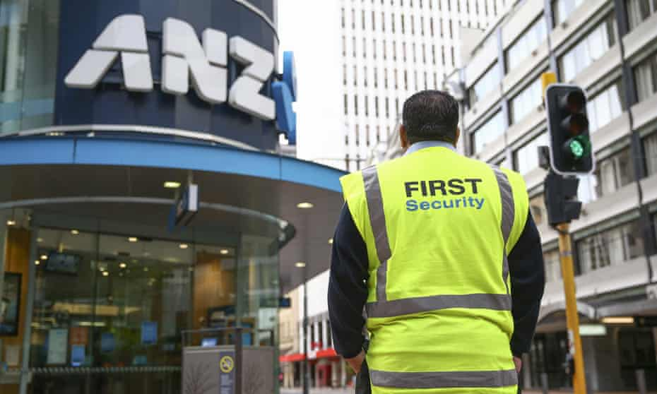 security guard in hi-viz stands outside an ANZ bank in Wellington, NZ