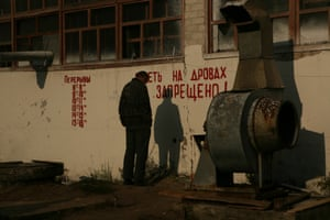 A man stands in front of a wall, waiting for his obligatory work hours to pass.