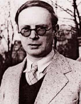 Grainy contemporary portrait of Voigt, clean-shaven, with slicked-down hair and thick-rimmed round glasses, wearing a shirt and tie, V-neck sweater and jacket