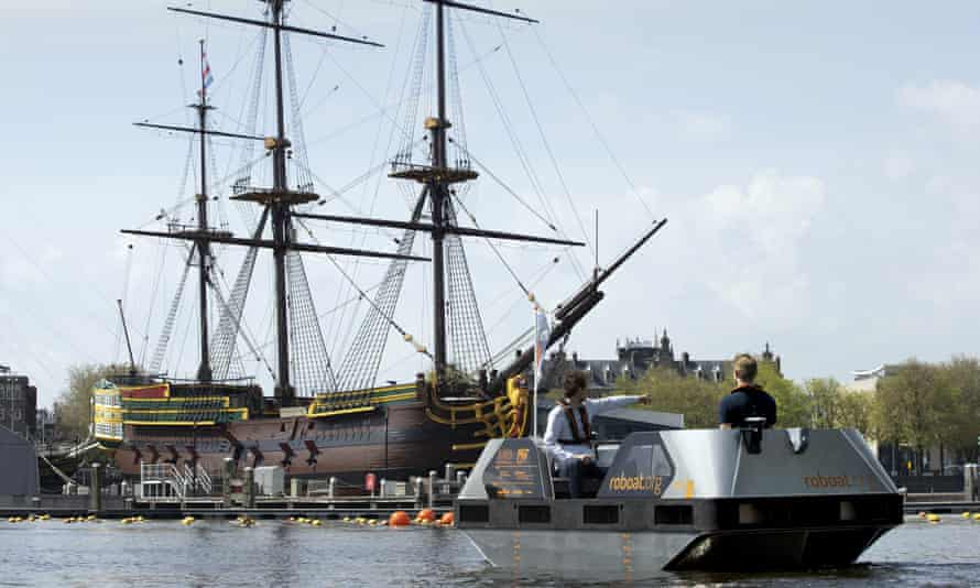 A Roboat steers close to a full-size replica of an 18th-century trading ship at the National Maritime Museum in Amsterdam.
