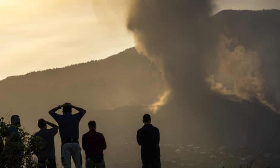 Residents look from a hill as lava continues to flow from the erupted volcano on La Palma in the Canary Islands on Friday.