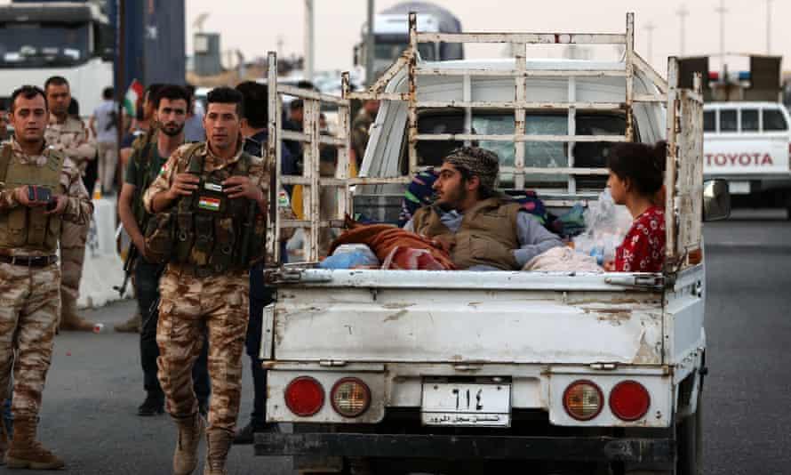 Iraqi families fleeing Kirkuk province cross a Kurdish checkpoint in Altun Kupri.